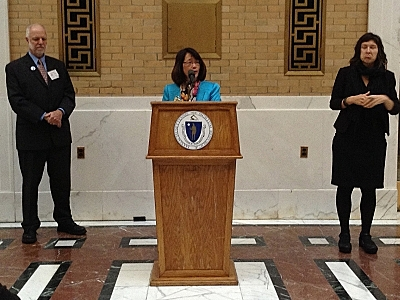 Lisa Wong of the Massachusetts Cultural Council speaking at a podiem flanked by Charles Washburn of VSA Massachusetts and an ASL-interpretor